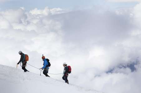 Three climbers in front of cloud on Mt Baker