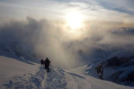 The sun breaking through the clouds while descending to 12K Camp on Denali
