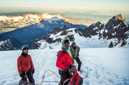 Three climbers taking a break while climbing Mt Baker