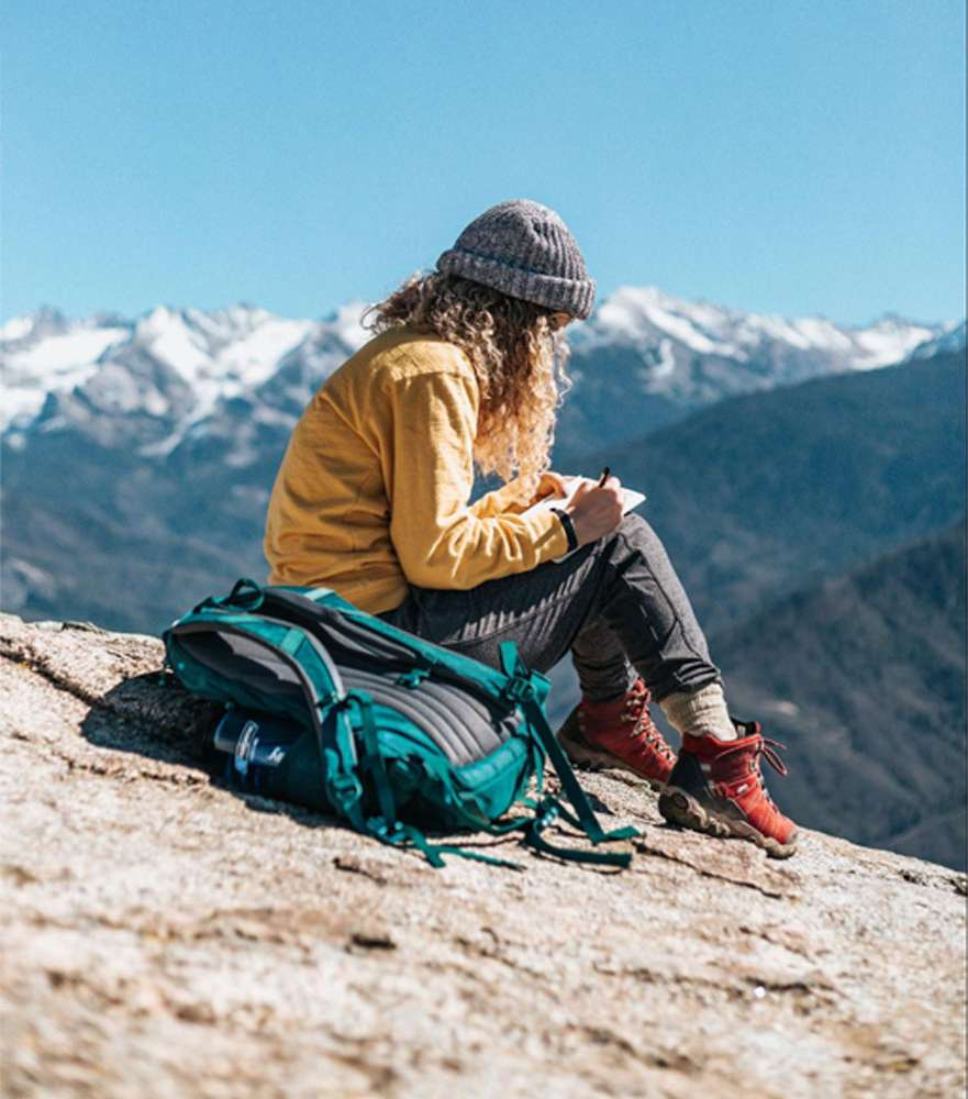 women-writing-in-journal-on-top-of-mountain
